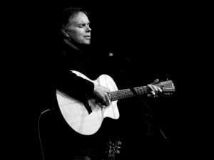 black and white photo of Leo Kottke playing an acoustic guitar signing into microphone