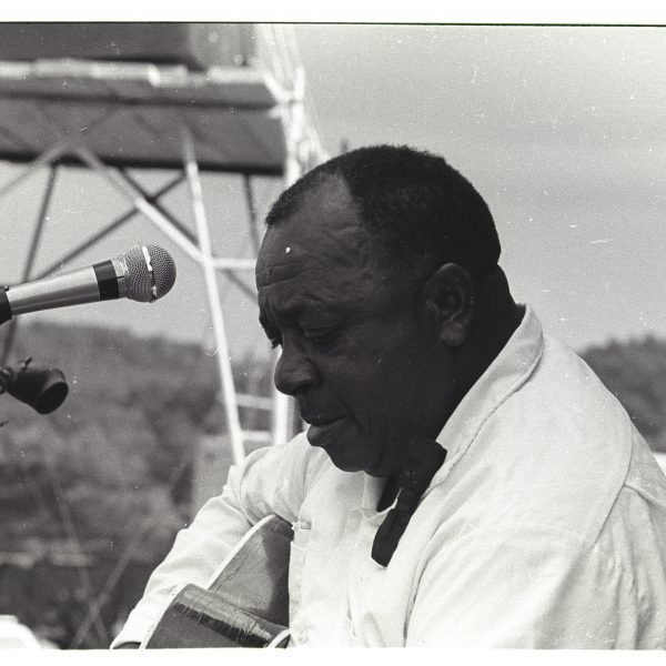black and white photo close up of a man playing an acoustic guitar on stage with a microphone in front of him