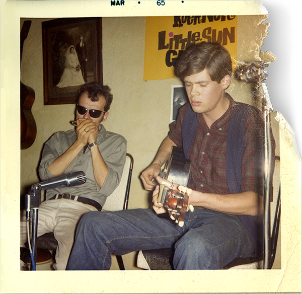 old photo of two men sitting in chairs one playing an acoustic guitar and the other wearing sunglasses playing a harmonica in front of microphones