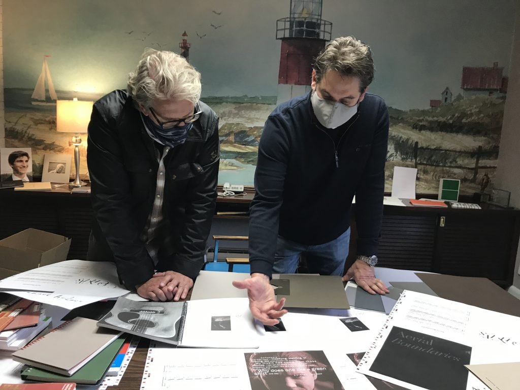 two men wearing masks leaning over table discussing transcriptions and a mural of a lighthouse by the sea in the background