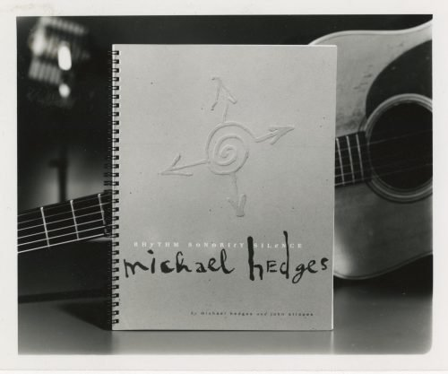 Michael Hedges Rhythm Sonority Silence transcription book cover with a swirl circle symbol and four arrows with an acoustic guitar in the background